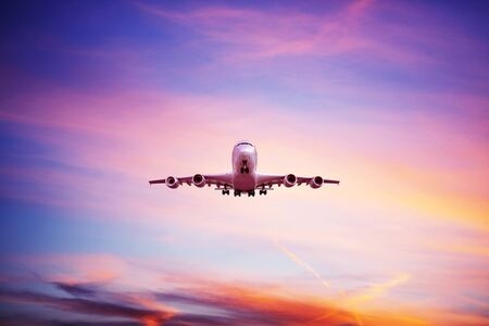 Airplane flying above dramatic clouds during sunset,sunrise