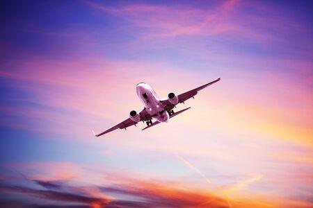 Avión volando por encima de las nubes dramáticas durante el atardecer, amanecer Foto de archivo