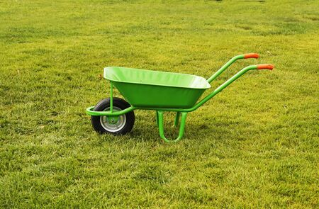 A green iron empty trash cart stands on the green grass,city services