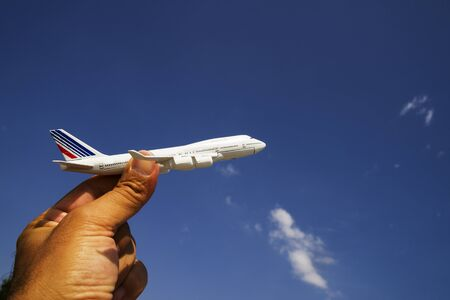 A man's hand holds a model airplane against a blue sky with white clouds