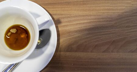A dirty white coffee cup stands on a wooden table. Leftover breakfast.