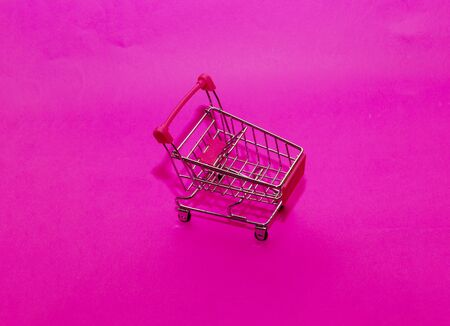 empty shopping cart on pink background. Shopping concept