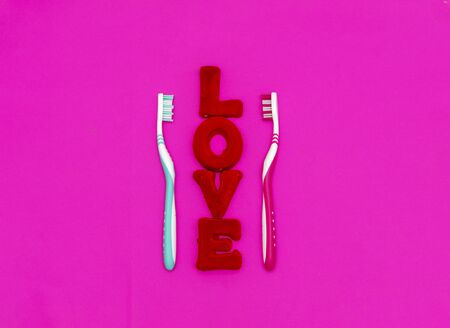 Two toothbrushes and the red word love on a pink background. The concept of clean, hygiene and love