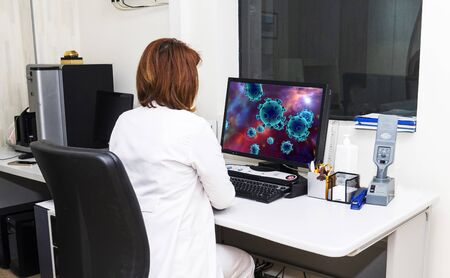 A female doctor examines coronaviruses on a computer, COVID-19
