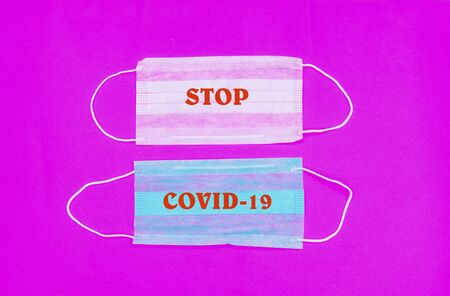 Novel Coronavirus 2019-nCoV , COVID-19 concept. protective medical mask with a red word COVID-19. vignette image. copy space.