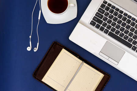 Modern workplace, laptop and accessories on a blue background top view.