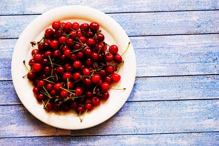Fresh cherry on plate on wooden blue background. fresh ripe cherries. sweet cherries Stockfoto