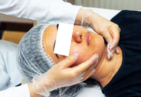 cosmetologist treats the girls face, a cosmetic procedure.