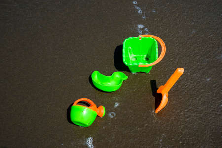childrens colored plastic toys lie on the sand in the sandbox. Zdjęcie Seryjne