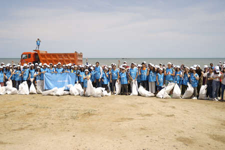 BAKU,AZERBAIJAN- 24 SEPTEMBER 2018 : Group of young students helping one another to clean up the beach, safe ecology concepts