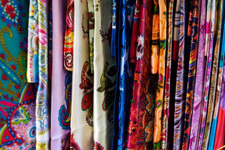 Oriental, Turkish, Indian multi-colored womens silk headscarves handmade on shop window for sale.