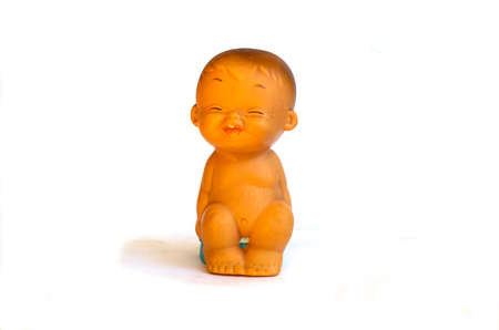 Rubber childrens old toy, little boy sitting on a pot, on a white background.