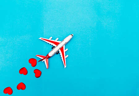 Airplane toy and heart on blue background, love travel concept