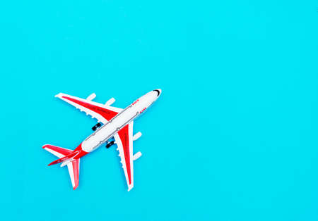 White and red Passenger Model airplane on a blue background. Free space for text. Travel concept