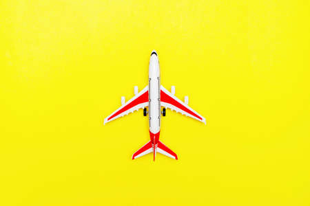 White and red Passenger Model airplane on a yellow background. Free space for text. Travel concept