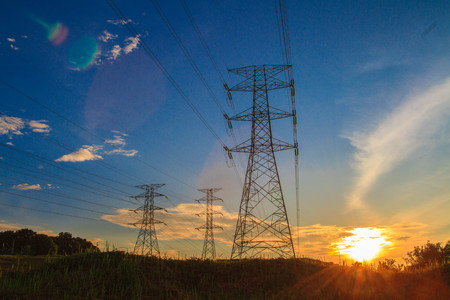 A high voltage of transmission tower in the morning sunrise with the beauty of a blue sky