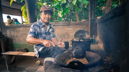 BALI, INDONESIA - 17TH JUNE 2015; Local farmer roasts coffee bean with traditional pan in Bali, Indonesia. Editorial