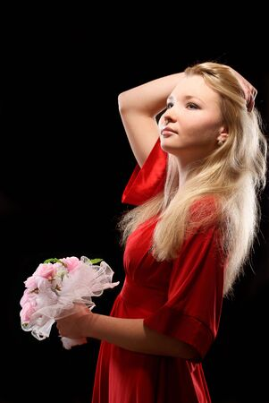 Young beatiful woman in red dress with flowers in her hand. Studio shot. Black background.