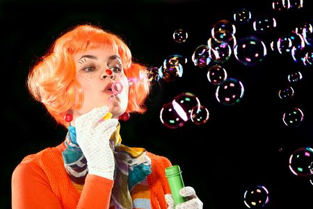 Clown girl making soap bubbles. Black background. Studio shot. Stock Photo