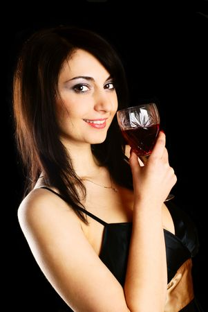 Portrait of a young woman with a glass of wine. Black background. Studio shot.