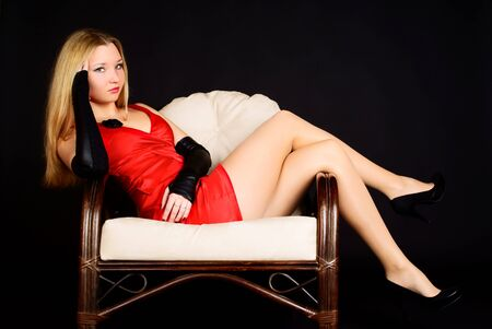 Beautiful sexy woman in red dress sitting in a chair. Studio shot. Stock Photo - 7174254