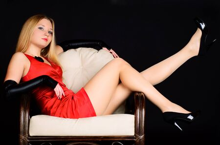 Beautiful sexy woman in red dress in a chair. Studio shot.
