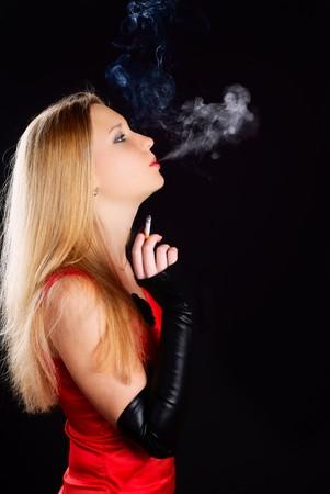 Woman in red dress smoking cigarette. Studio shot.
