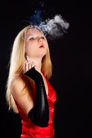 Sexy woman in red dress smoking cigarette. Studio shot. photo