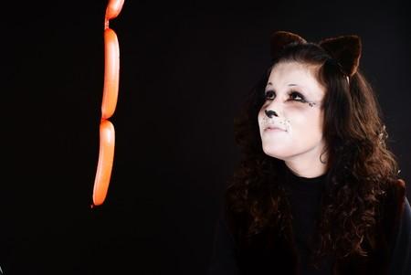 Portrait of cat girl wathcing at sausage. Studio shot. Stock Photo