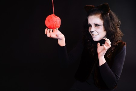 Cat-girl playing with threads ball. Studio shot.