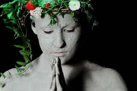 Preying mother earth. Black background. Studio shot. photo
