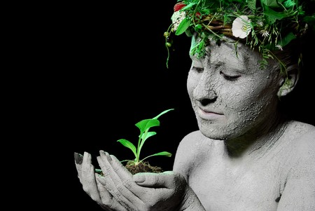 Mother earth holding plant sprout in her hands. Black backgroung. studio shot. Stock Photo