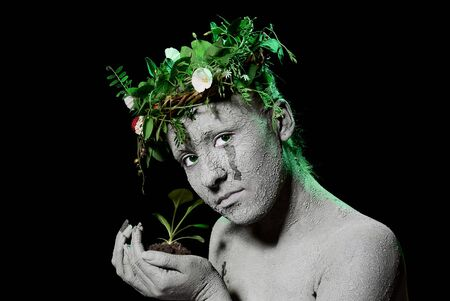 Mother earth holding plant sprout in her hands. Black backgroung. studio shot. Stock Photo - 7656391
