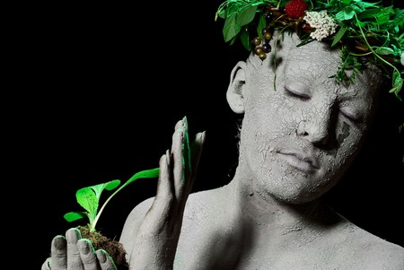 Mother earth holding plant sprout in her hands. Black backgroung. studio shot. Stock Photo - 7656396