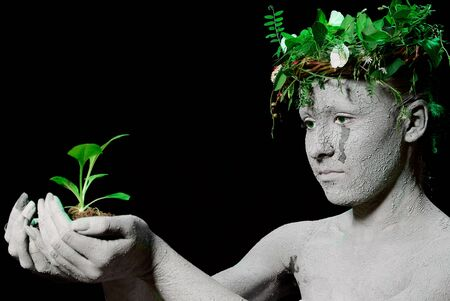 mother earth: Mother earth holding plant sprout in her hands. Black backgroung. studio shot. Stock Photo