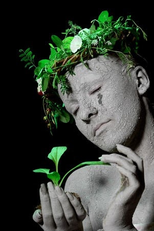 Mother earth holding plant sprout in her hands. Black backgroung. studio shot. photo