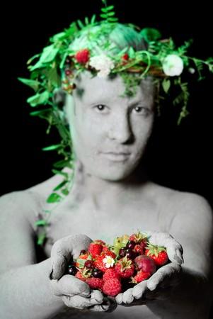 Mother earth holding berries in her hands. Black background. Studio shot.