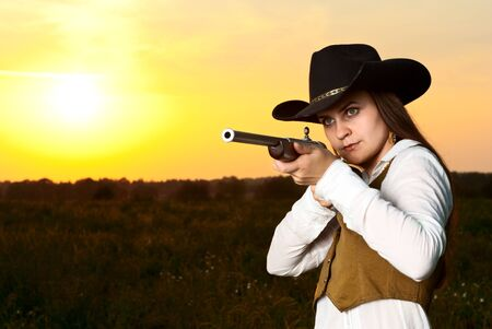 Cowboy woman with a gun in a sunset time. Stock Photo