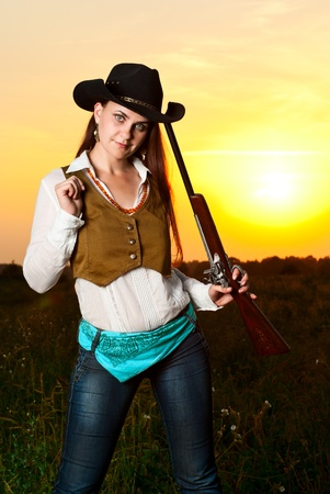 Cowboy woman with a gun in sunset time. Stock Photo