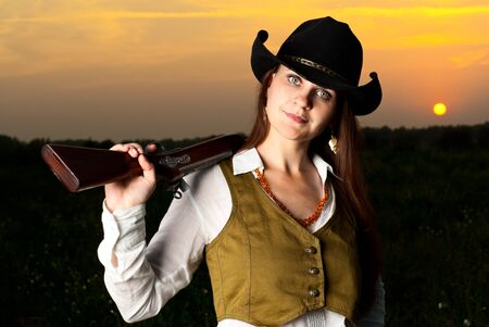 Cowboy woman with a gun in a sunset time.