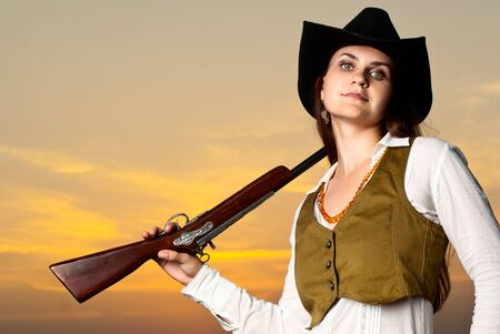 Cowboy woman with a gun in a sunset time. photo