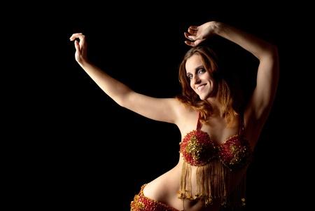 Dancing young sexy woman. Black background. Studio shot.