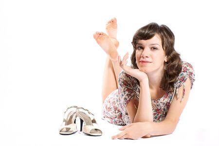 whithe: Woma, tumbado en el suelo con un zapatos. Fondo de Whithe. Estudio de un disparo.