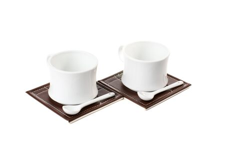 Two empty tea cups with spoons on table mats. Isolated on white background.