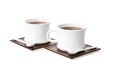 Twee kopjes met thee, twee spons op tafelmatten. Geïsoleerd op witte backgrond.