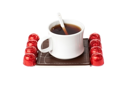 trivet: A cup of tea with sweets. Isolated on white background.