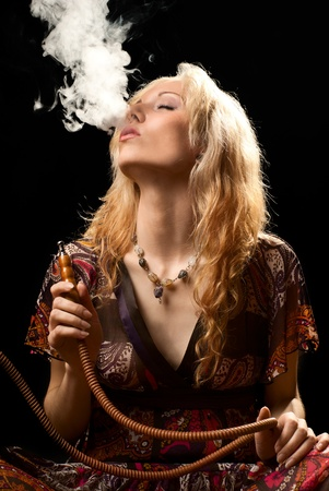 Potrait of a woman smoking hookah. Black background. Studio shot.