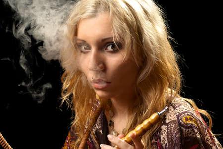 Portrait of a woman smoking hookah. Black background. Studio shot. photo