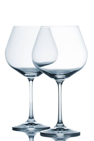 Two empty wine glasses on white background