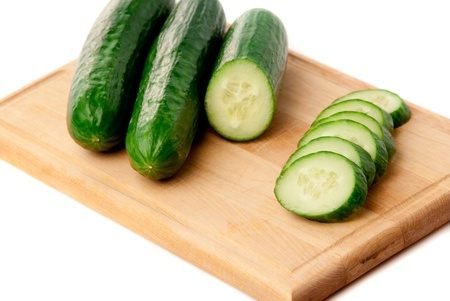 sliced cucumbers on the carving board. White background. studio shot.